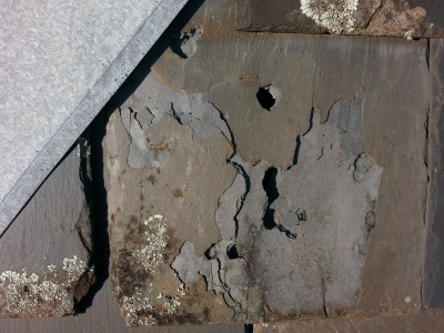 deteriorated soft porous and damaged slate roof tiles